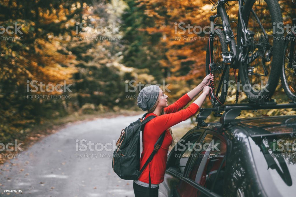 Woman picking up bikes from car roof rack to start adventure stock photo