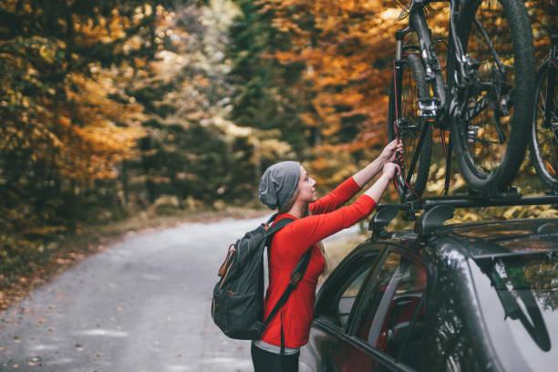 frau, die abholung der fahrräder aus auto dachträger abenteuer zu beginnen - fahrradträger stock-fotos und bilder