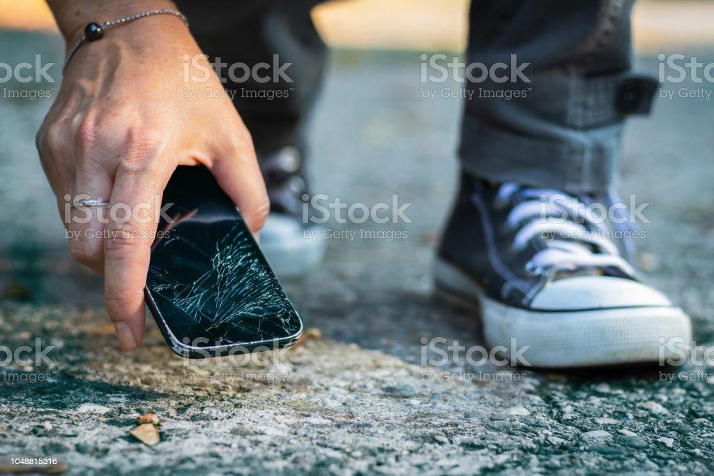 Frau Gebrochen Smartphone Aus Dem Boden Aufnehmen Stock Fotografie