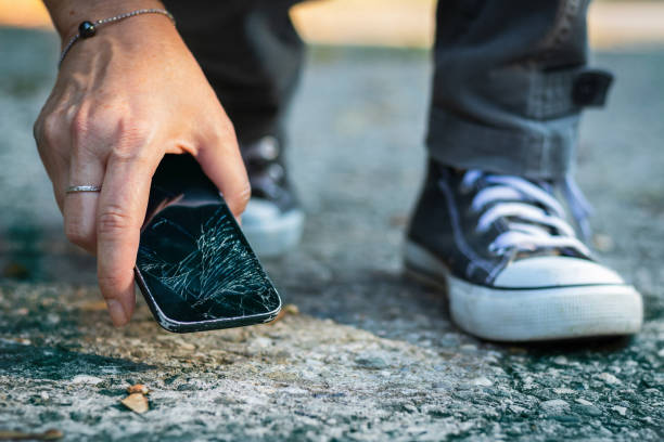 Woman picking up broken smartphone from the ground. stock photo