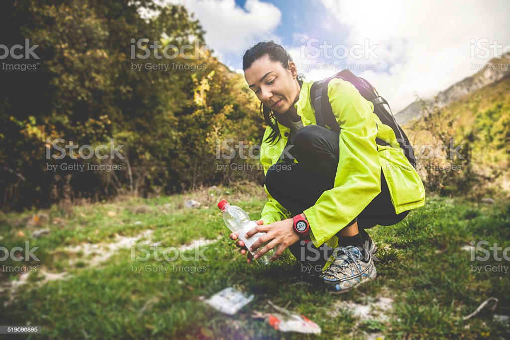 Woman picking up litter in mountain stock photo