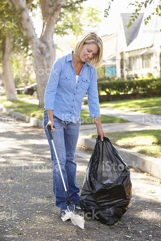 Woman Picking Up Litter In Suburban Street royalty-free stock photo