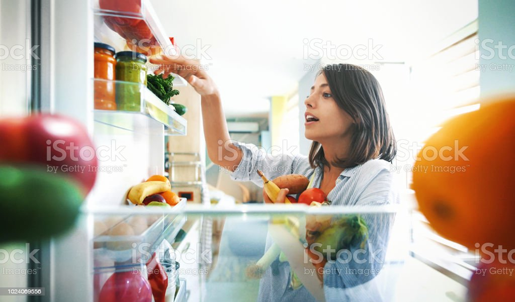 Woman picking up some fruits and veggies from the fridge stock photo