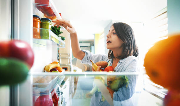 woman picking up some fruits and veggies from the fridge - healthy food imagens e fotografias de stock
