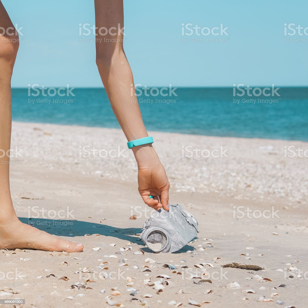 Woman picking up trash in the sea stock photo