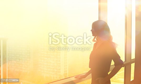 CEO woman looking out skyscraper window dreaming big