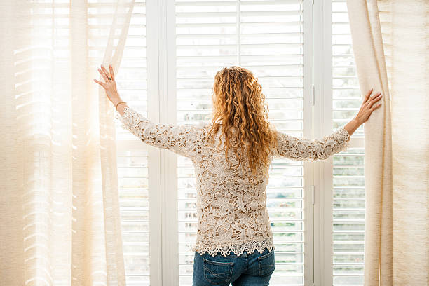 a woman pictured looking out of a window - blinds stock pictures, royalty-free photos & images