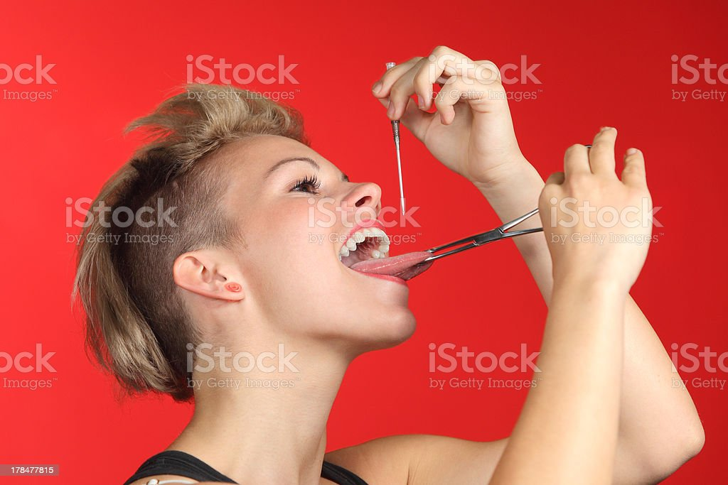 Woman piercing the tongue herself royalty-free stock photo