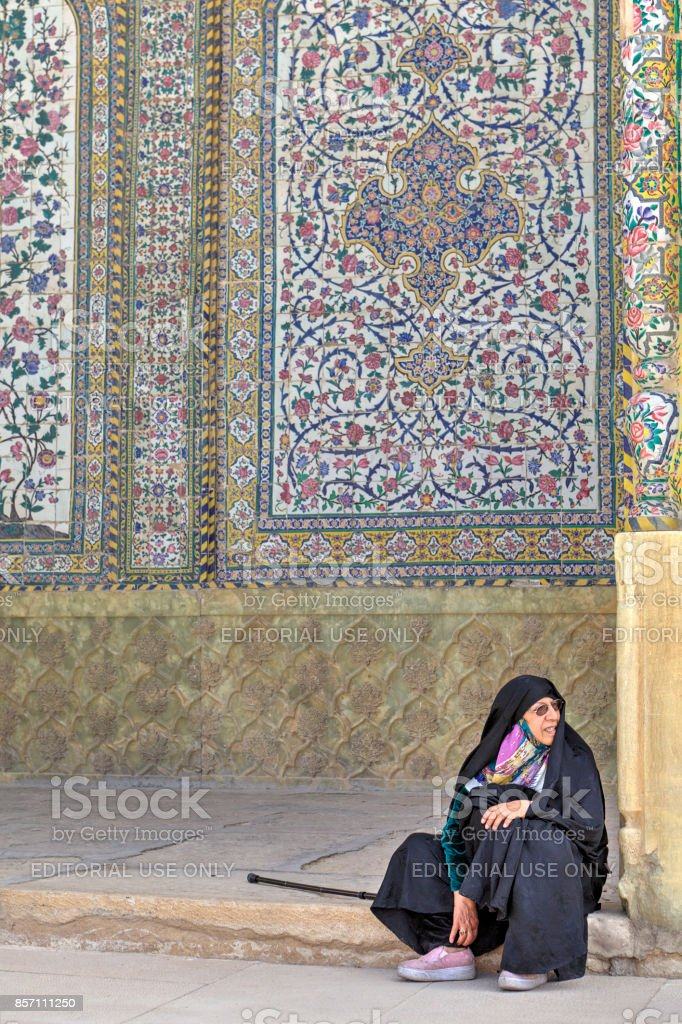 Woman pilgrim dressed in Islamic clothing, sitting inside holy place. stock photo