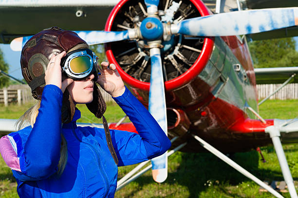 woman pilot in helmet on background of airplane woman pilot in helmet on background of airplane closeup flight suit stock pictures, royalty-free photos & images