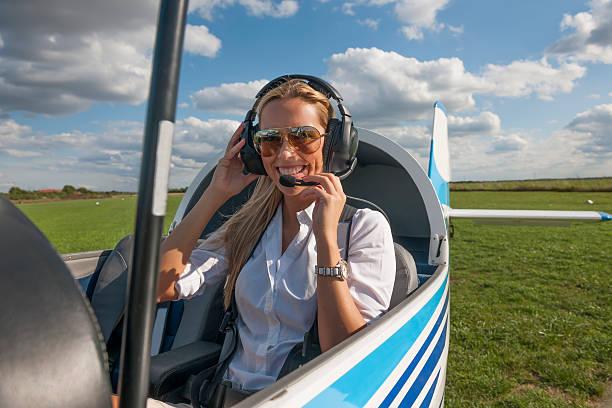 frau pilot blick in die kamera, die vorbereitung für flying - flugschule stock-fotos und bilder