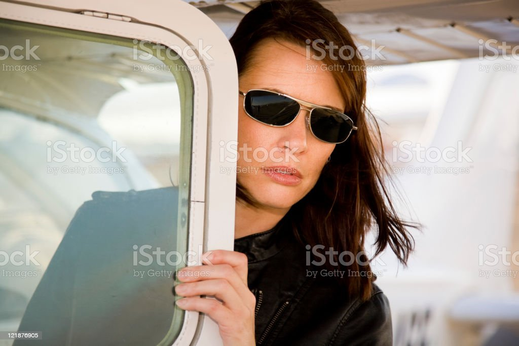 Woman Pilot Standing Next to an Airplane stock photo
