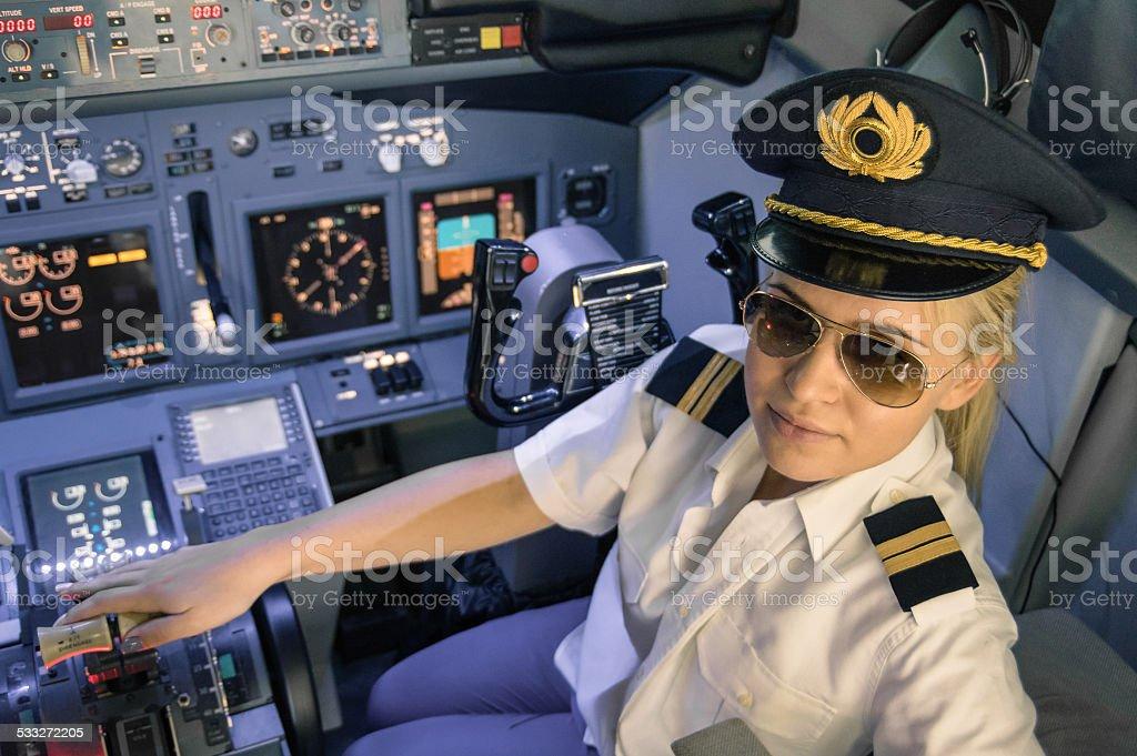 Woman pilot wearing uniform in flight simulator cockpit stock photo