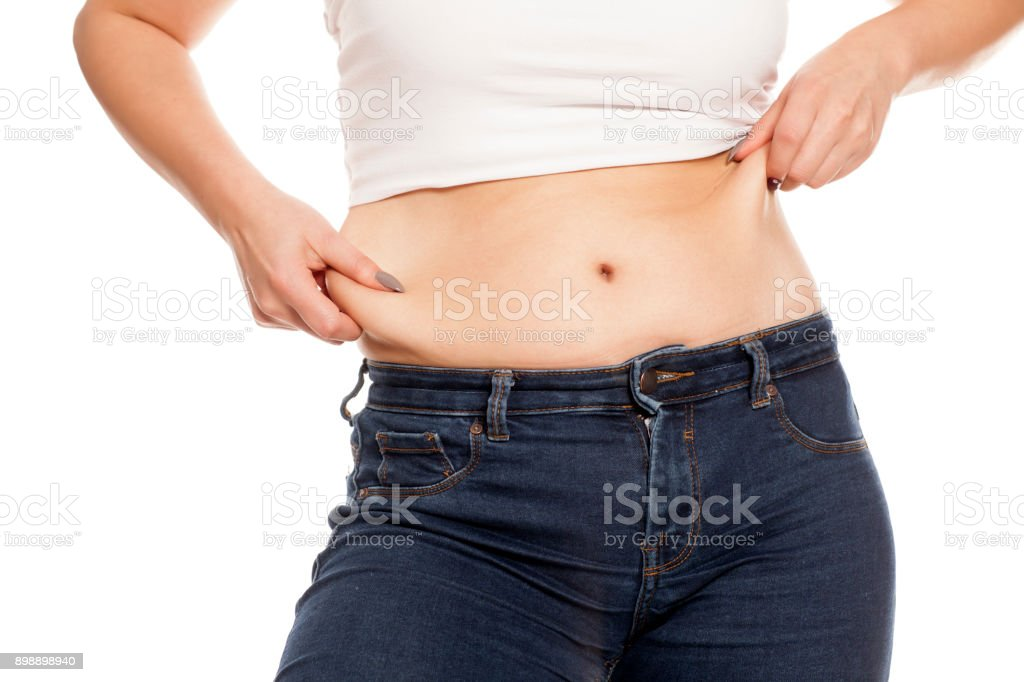 woman pinches her fat on her belly stock photo