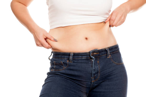 woman pinches her fat on her belly - human abdomen stock pictures, royalty-free photos & images