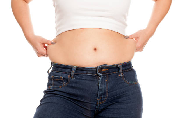 woman pinches her fat on her waist stock photo