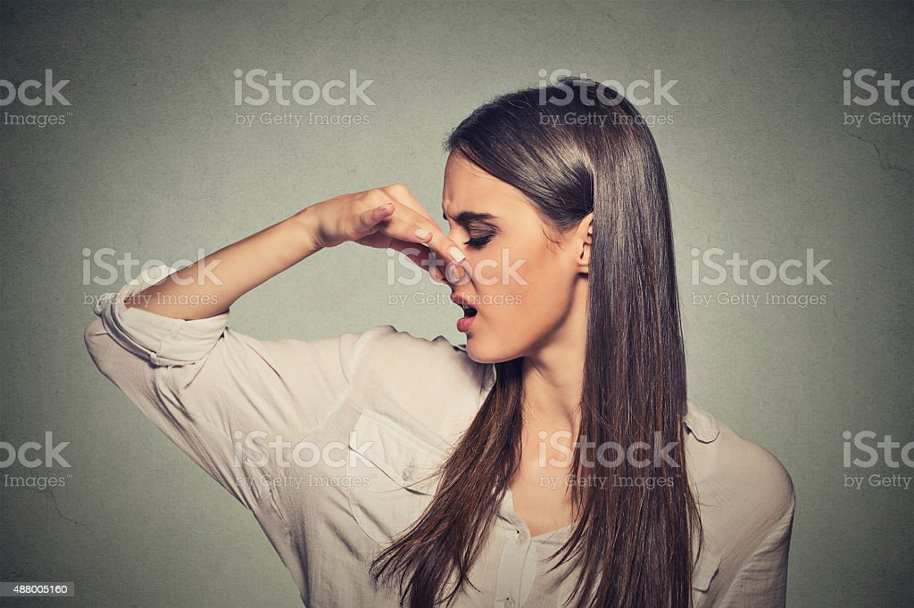 woman pinches nose looks with disgust something stinks stock photo