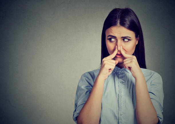 woman pinches nose with fingers looks with disgust away something stinks bad smell - scented stock photos and pictures