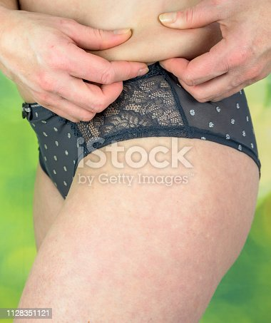 521792745 istock photo Woman pinching belly for skin fold test 1128351121