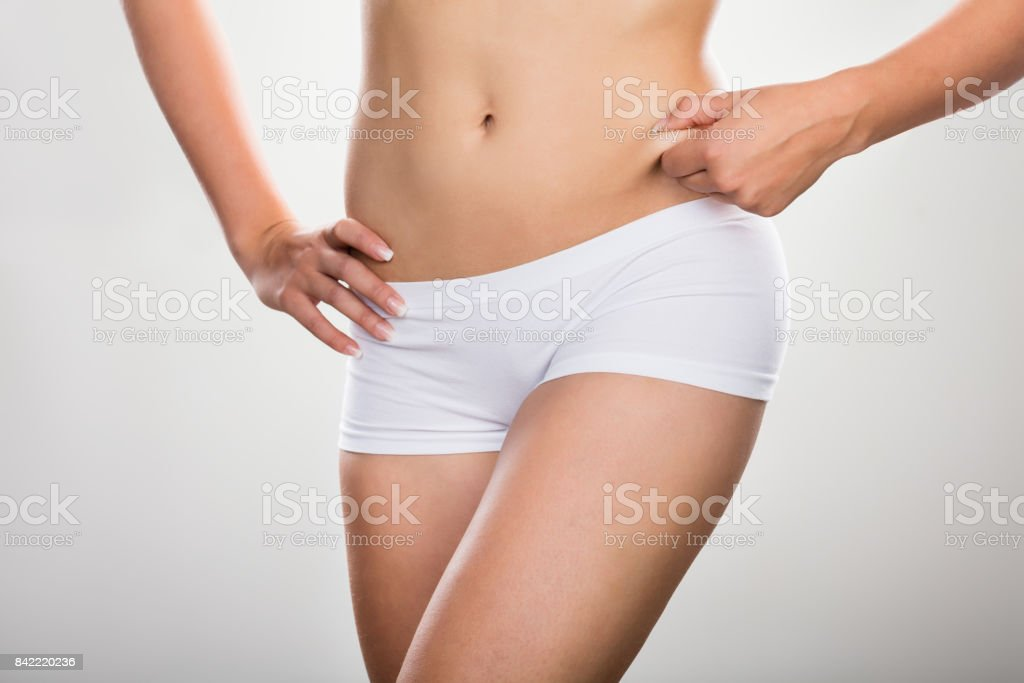 Woman Pinching Excessive Stomach Fat stock photo