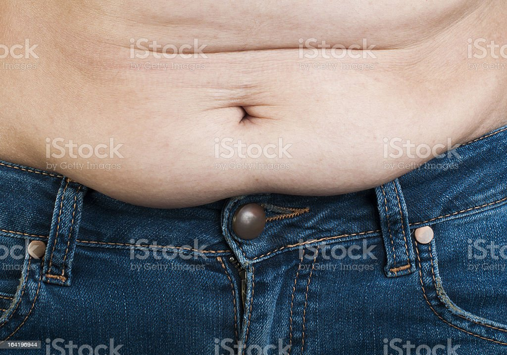 Woman pinching fat from her abdomen royalty-free stock photo