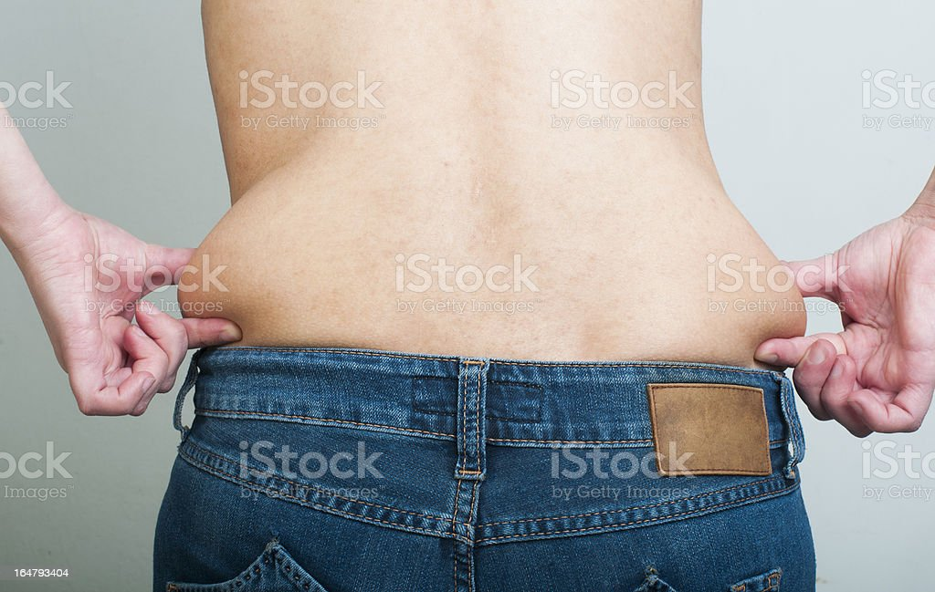 Woman pinching fat from her waist royalty-free stock photo