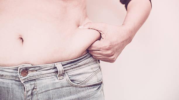 Woman Pinching Fat on her waist stock photo