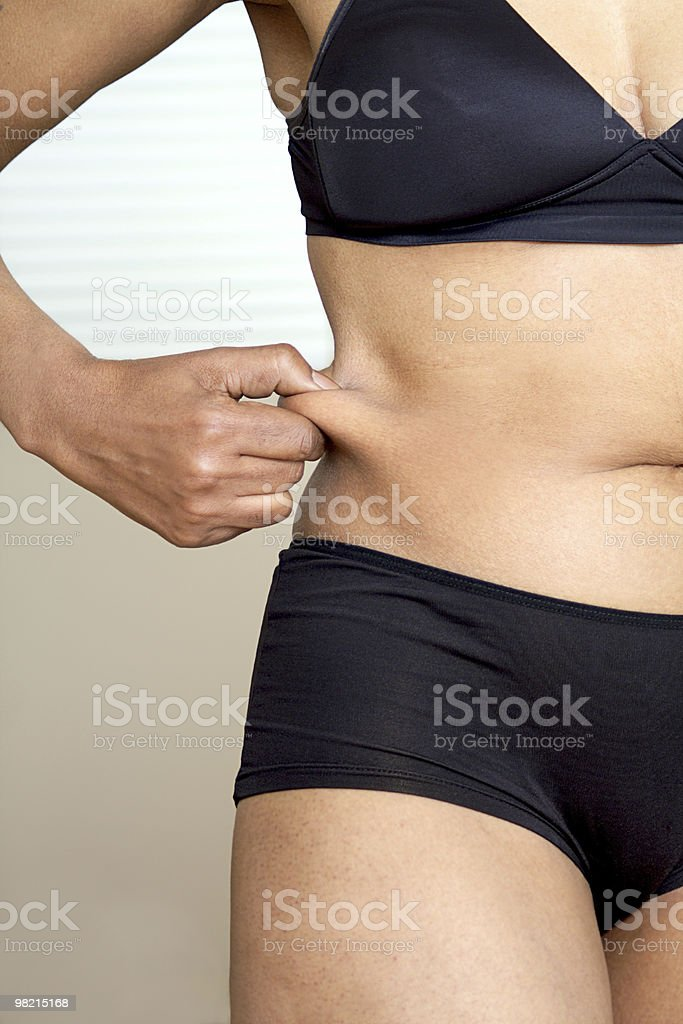 Woman pinching waist royalty-free stock photo
