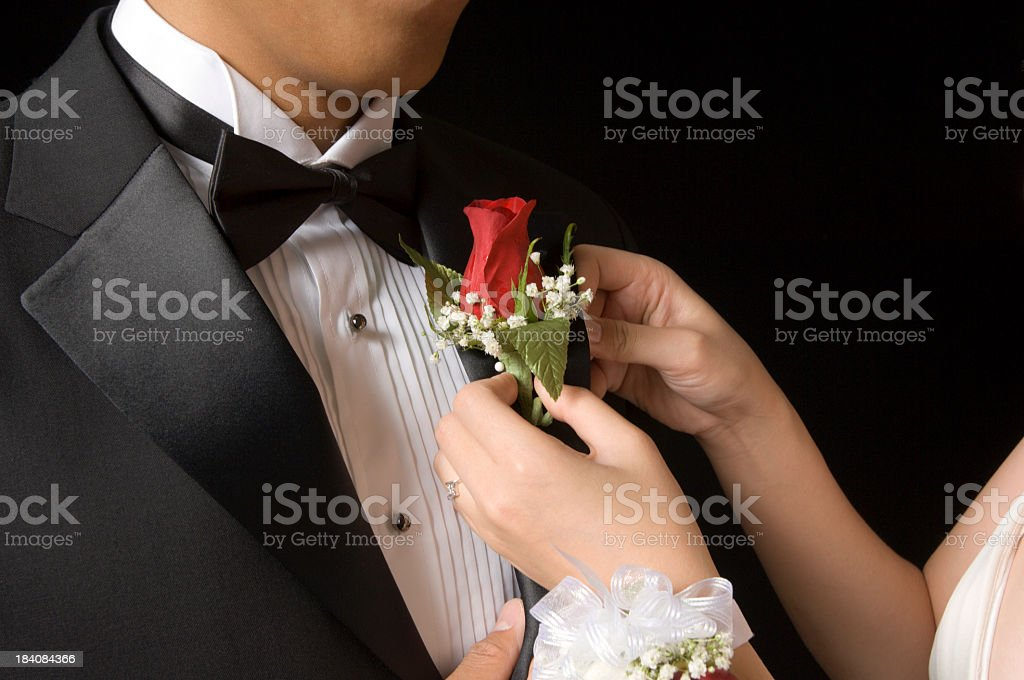 Woman pinning boutonniere on man's lapel royalty-free stock photo
