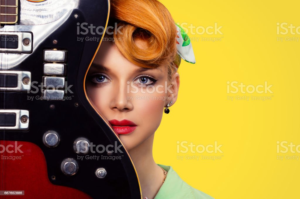 Woman pinup girl with electric acoustic rock guitar isolated yellow background stock photo