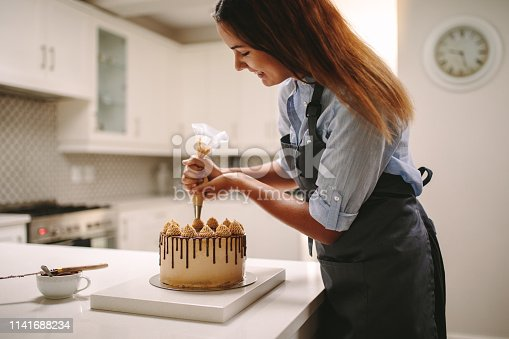 Female chef decorating cake with whipped cream using party bag. Woman in apron preparing a delicious cake at home.