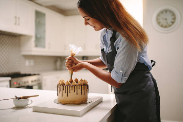 Woman piping decoration on a cake Female chef decorating cake with whipped cream using party bag. Woman in apron preparing a delicious cake at home. cake stock pictures, royalty-free photos & images