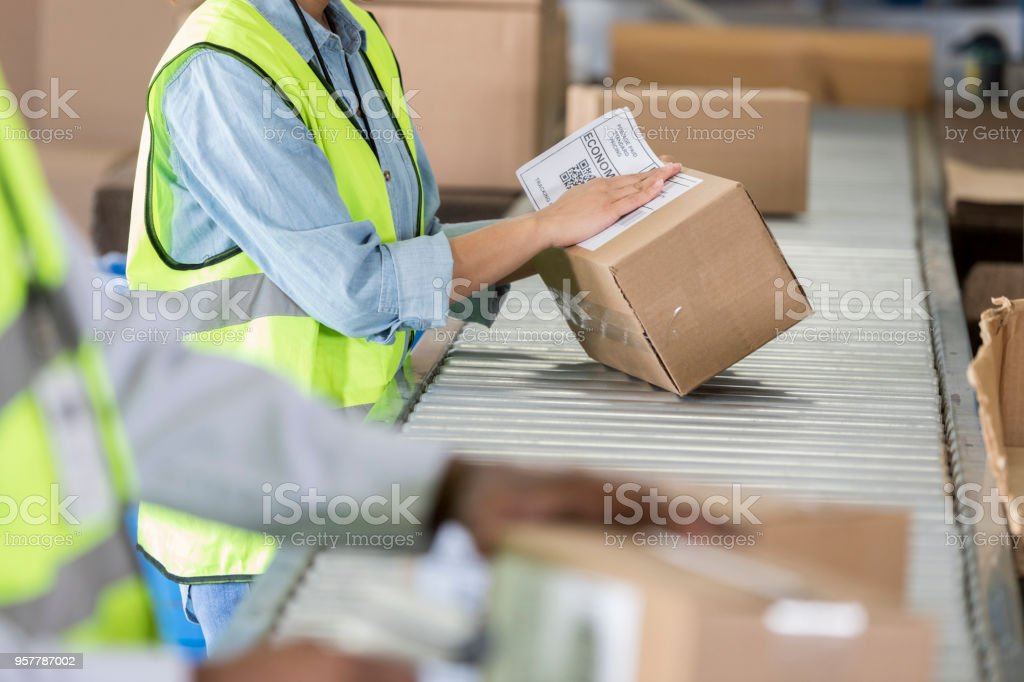 Unrecognizable woman working in warehouse places mailing label on...