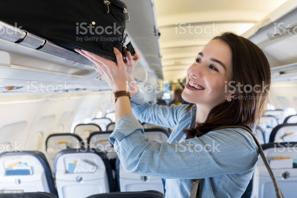 Woman places luggage in airplane's overhead compartment Confident female business traveler places a carryon luggage item in an overhead compartment. Adult Stock Photo