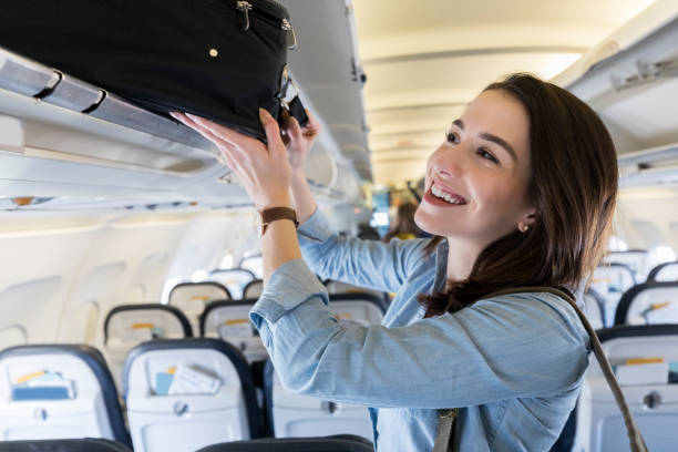 Woman places luggage in airplane's overhead compartment Confident female business traveler places a carryon luggage item in an overhead compartment. carry on luggage stock pictures, royalty-free photos & images