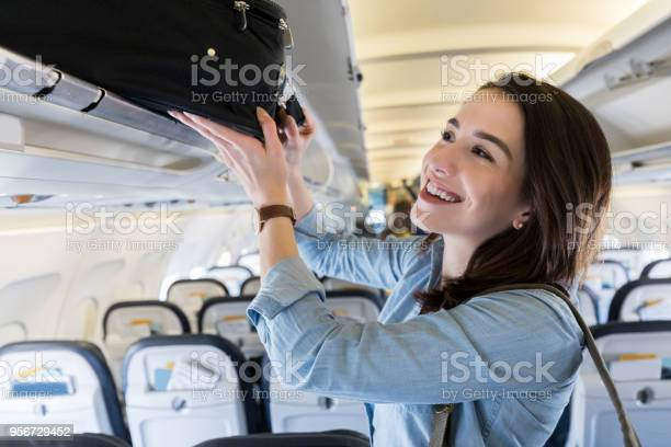 Woman Places Luggage In Airplanes Overhead Compartment Stock Photo - Download Image Now