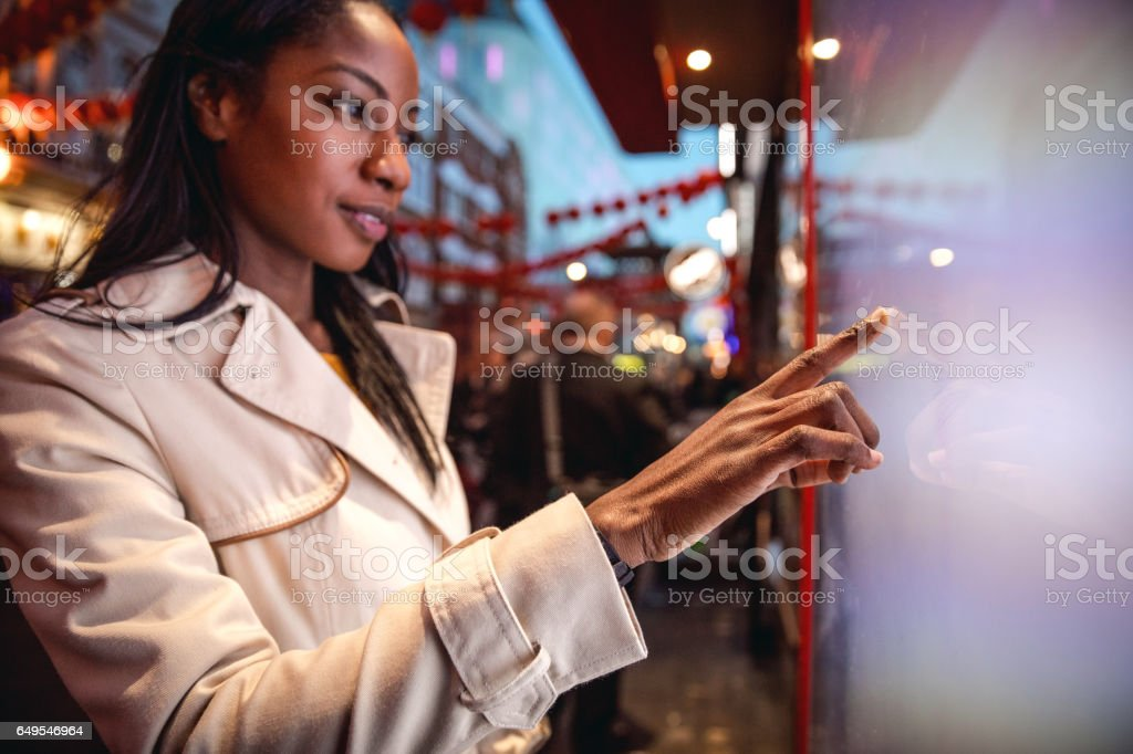 Woman placing an order using a touch screen stock photo
