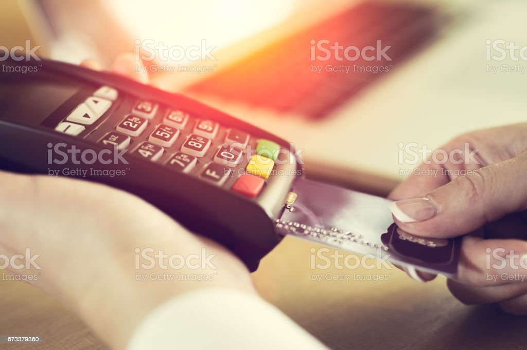 Woman placing credit card into reader stock photo