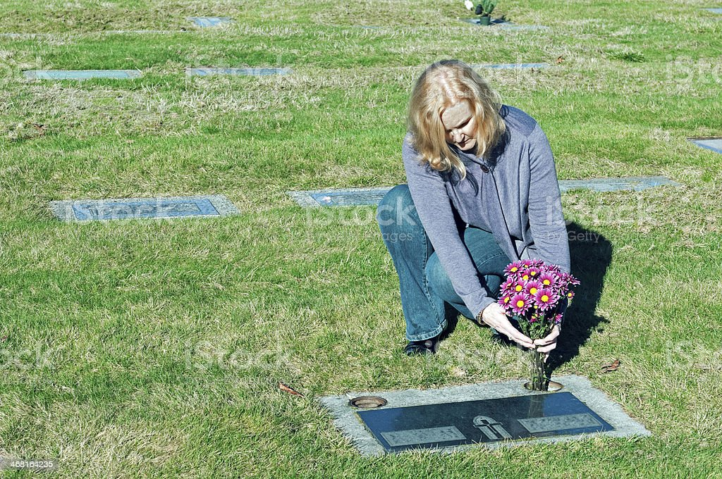 Woman placing flowers at grave in cemetery royalty-free stock photo