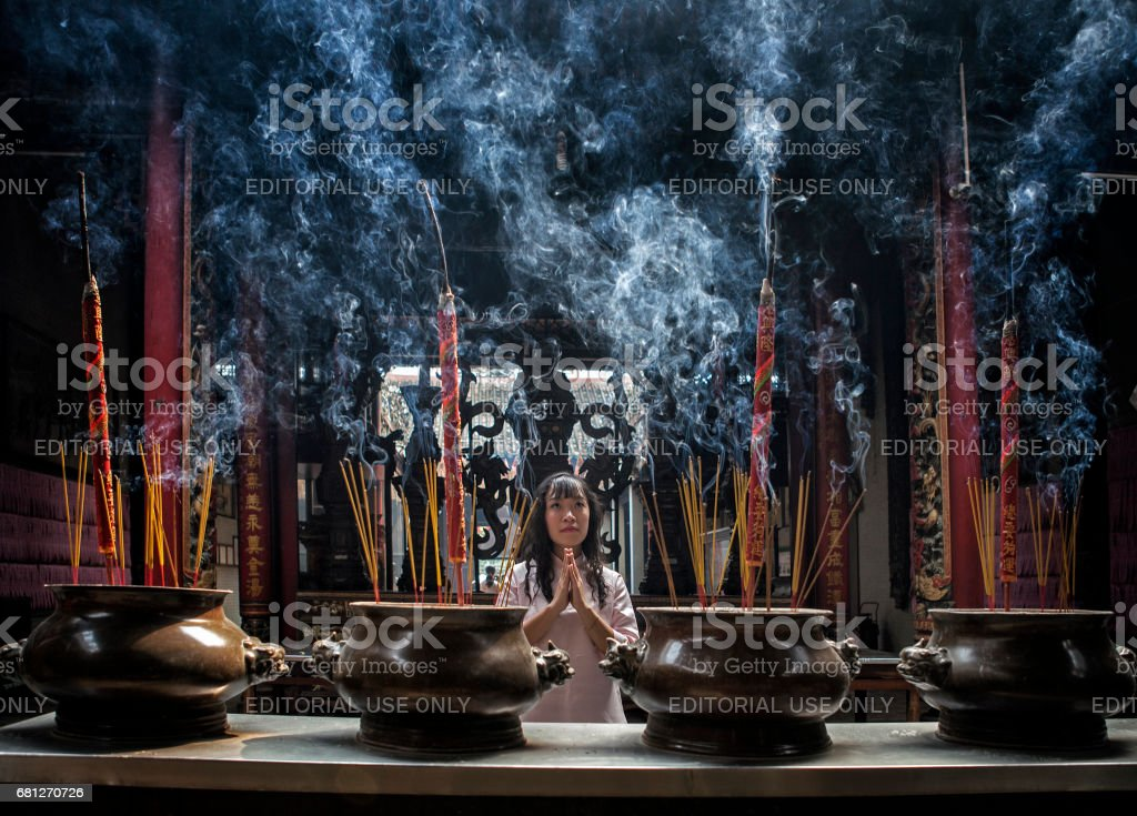 Woman Placing Incense Sticks In A Vietnamese Temple royalty-free stock photo