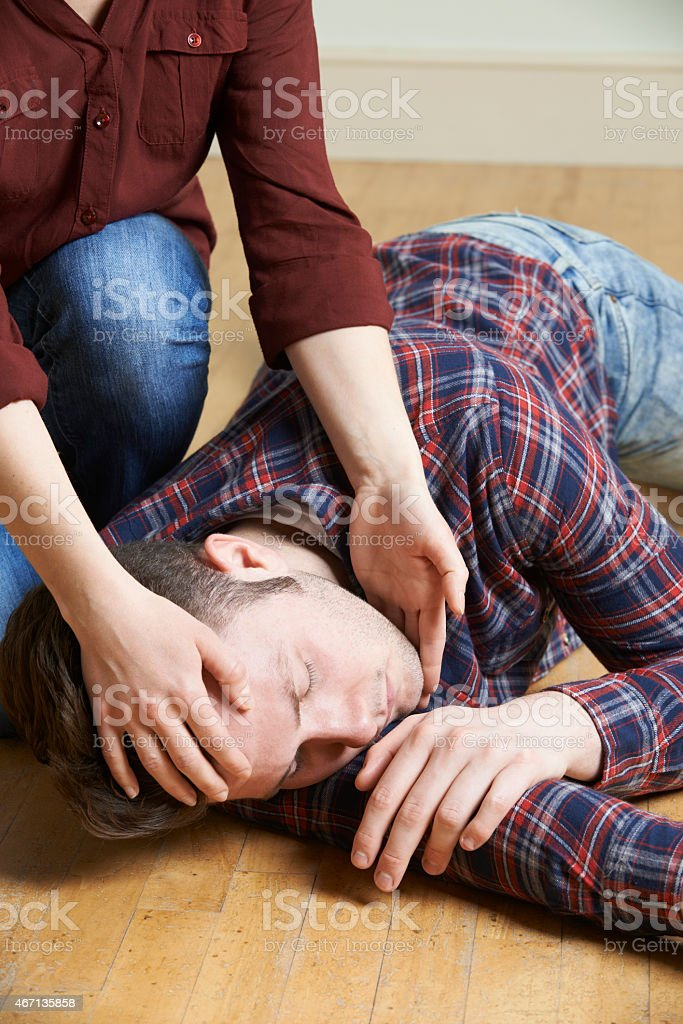 Woman Placing Man In Recovery Position After Accident stock photo