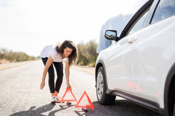woman placing red warning sign by broken car - stranded stock pictures, royalty-free photos & images