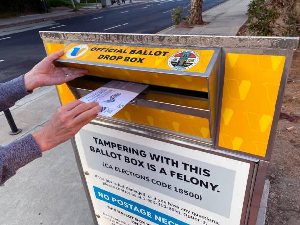 woman placing voting ballot in official 2020 drop box - biden стоковые фото и изображения