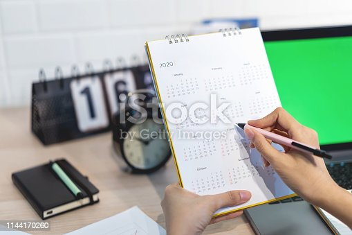 1186985932 istock photo Woman planning agenda and schedule using calendar event planner. Calender planner organization management remind concept. 1144170260
