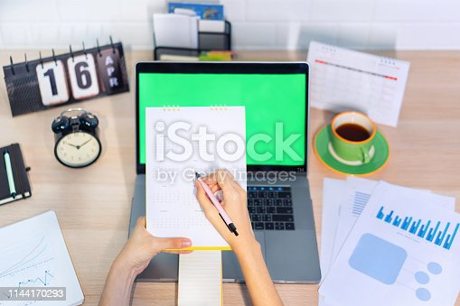 1186985932 istock photo Woman planning agenda and schedule using calendar event planner. Calender planner organization management remind concept. 1144170293