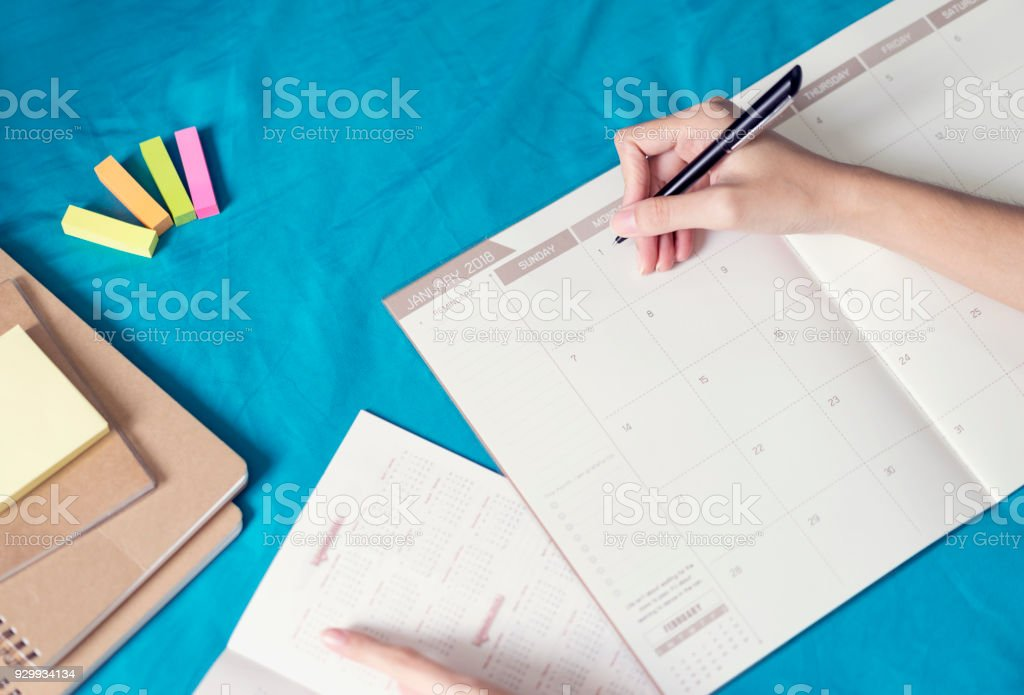 Woman planning agenda and schedule using calendar event planner, Writing plan on memo schedule. Woman hands using plan to vacation on Happy New Year 2018. stock photo