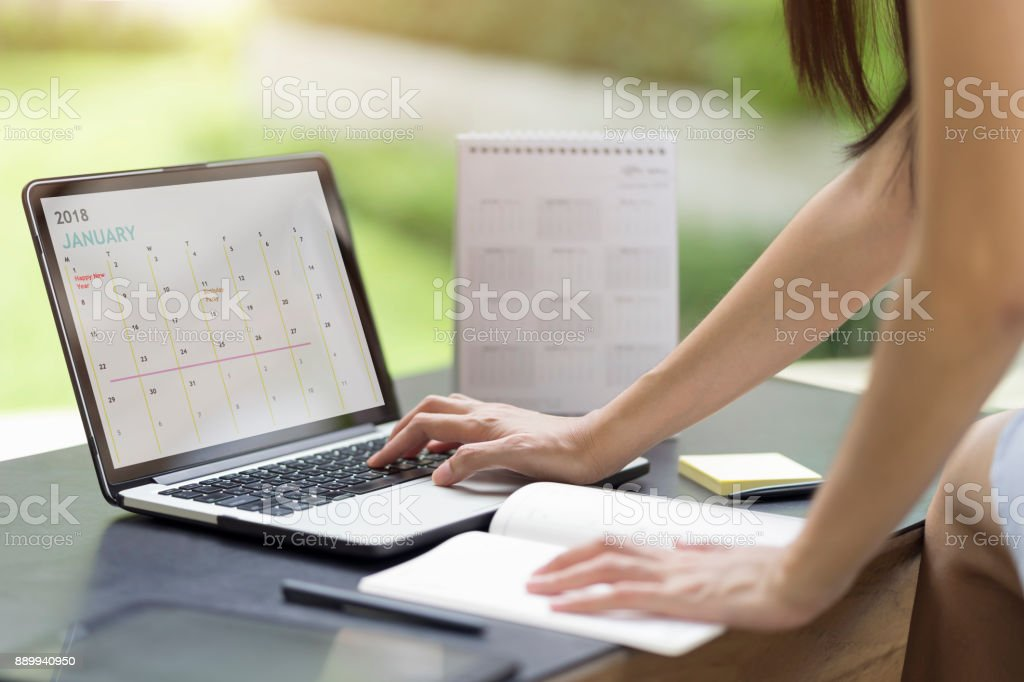 Woman planning agenda and schedule using calendar event planner. Woman hands using plan to vacation on computer laptop. Calender planner organization management remind concept. stock photo