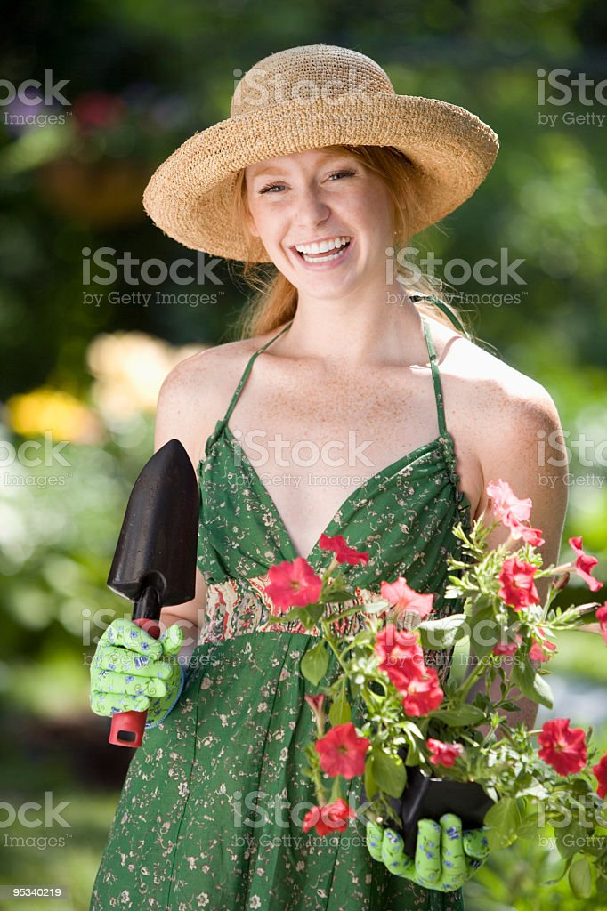 Woman planting flowers in her garden royalty-free stock photo