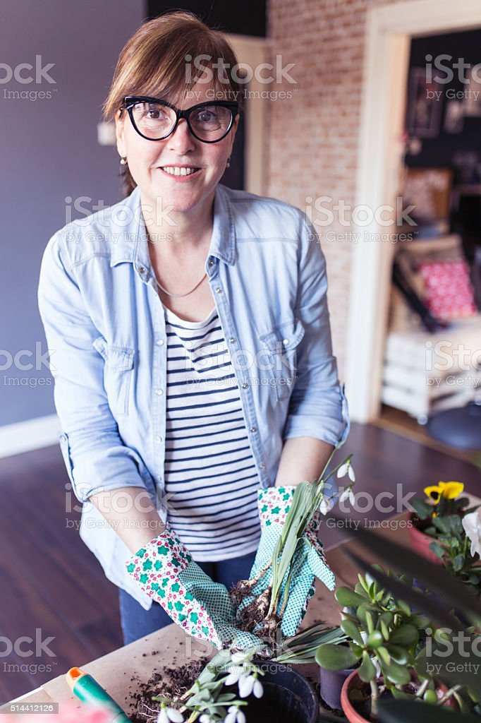 Woman planting flowers in her home garden stock photo