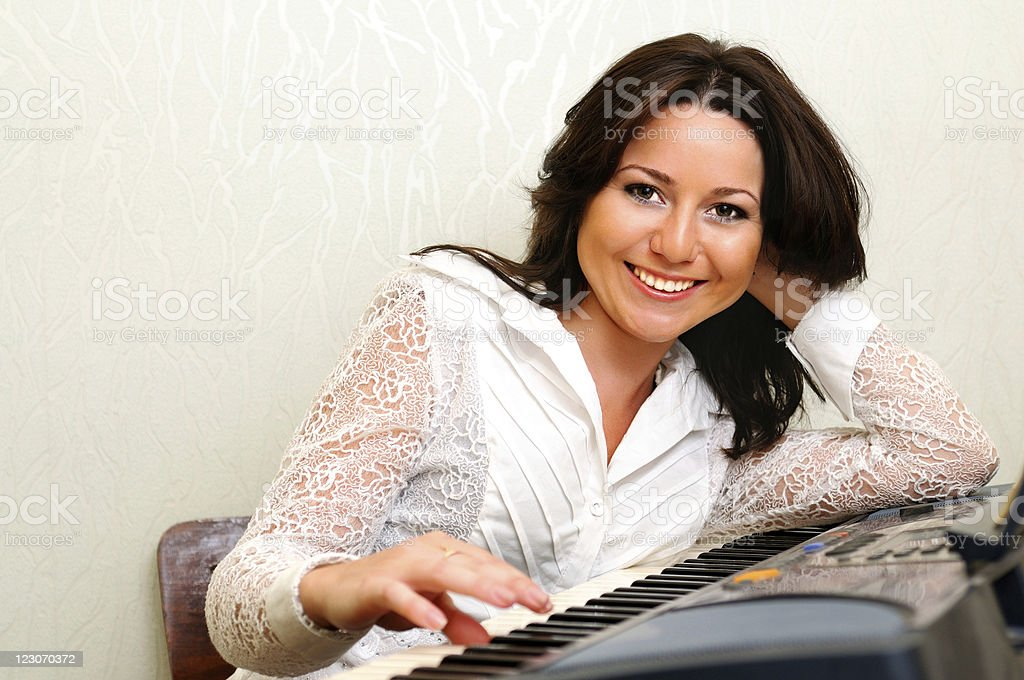 Woman play on synthesizer royalty-free stock photo